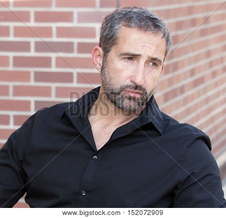 portrait of handsome man in his 40s looking very sad