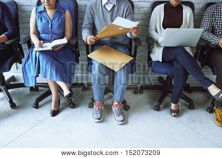 Business people sitting on chairs along the wall and working