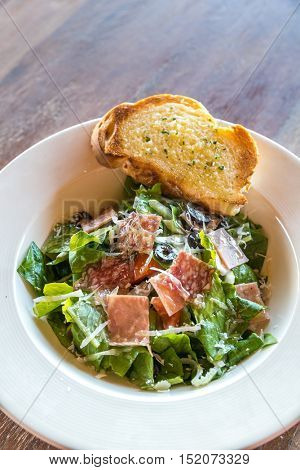 Caesar Salad with parma ham on wooden table
