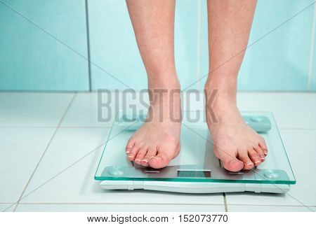 Close Up Of Woman Feet Weighing In Bathroom