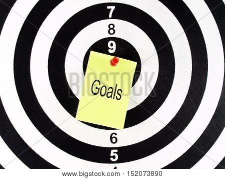 goals word on yellow note with red pushpin on target center of dartboard, aim and achievement concept
