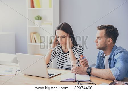 Just try it. Good looking young man holding glass of water and offering pill to his pretty colleague while working on laptop.