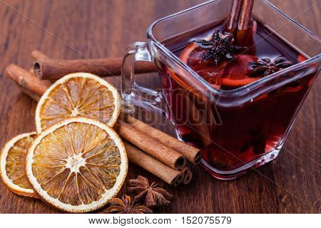 Mulled wine and spices on wooden table