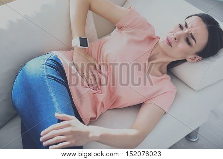 Bad health.Unhappy young woman having stomachache and touching her belly while laying on the sofa.