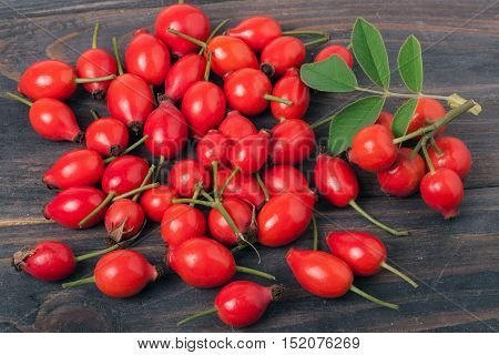 fresh rose hips with leaves on a dark wooden background.