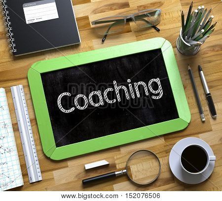 Coaching Concept on Small Chalkboard. Coaching Handwritten on Green Chalkboard. Top View Composition with Small Chalkboard on Working Table with Office Supplies Around. 3d Rendering.