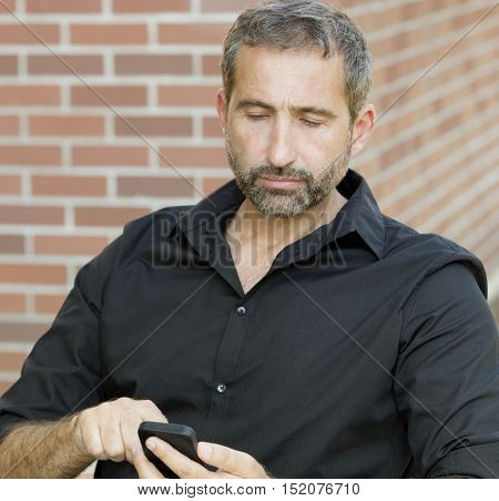 portrait of handsome businessman in his 40s texting on his phone