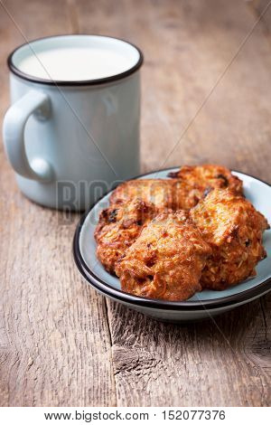 carrot oatmeal cookies with raisins on the blue plate glass of milk on the old wooden background