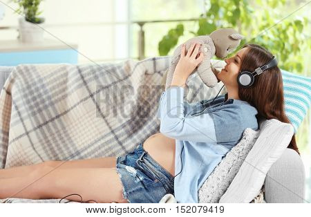 Pregnant woman listening to music with teddy bear on sofa
