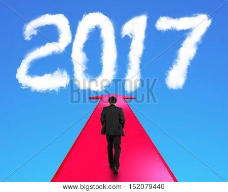 Businessman walking on red arrow going upward toward white 2017 year shape clouds in blue sky.