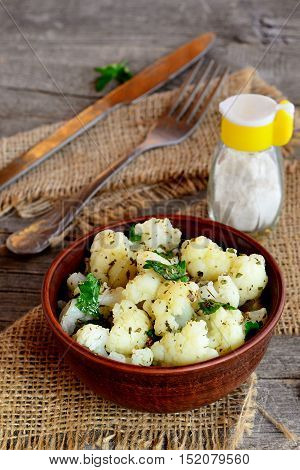 Pickled cauliflower with spices and parsley. Pickled cauliflower in an earthenware bowl and on an old wooden table. Rustic style. Closeup