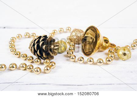 Brilliant gold cones like christmas decoration. Yellow cones and balls isolated on white wooden background.