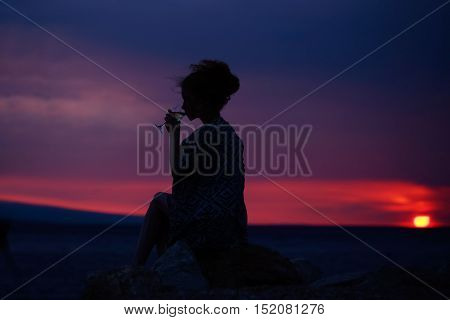 pretty sexy female silhouette of woman or girl with wine glass outdoor over dramatic dark sky with clouds and sea or ocean water horizon on evening or twilight natural sunset background