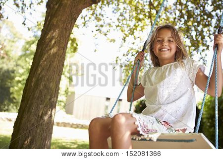 Portrait Of Young Girl Playing On Tree Swing