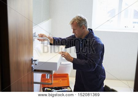 Plumber Mending Sink Tap In Bathroom