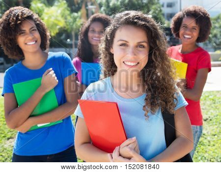 Group of four latin and caucasian female students outdoor in the city in summer