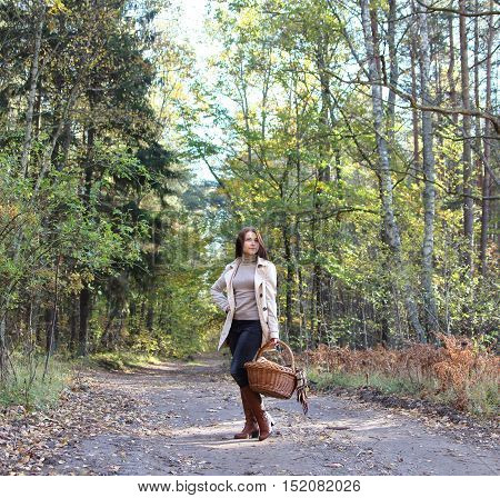 girl with a wattled basket and a checkered plaid in autumn forest