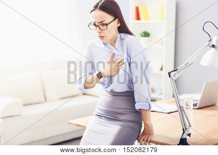 Shocking news. Pretty bespectacled woman leaning on the table and putting hand on her heart while having heartache.