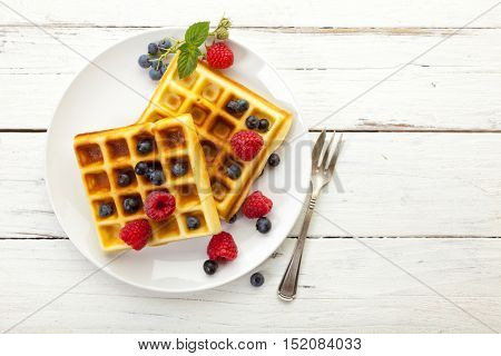 High angle view of Belgian waffles with blueberry and raspberry fruit on white plate, on rustic table, copy space