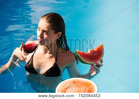 young sexy woman or girl with pretty face and wet hair swimming in pool with blue water eating red watermelon and drinking wine from glass sunny summer day outdoor