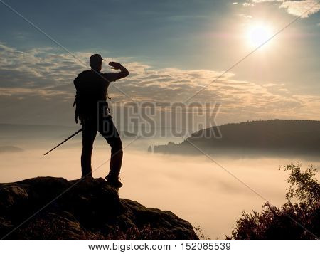 Hiker Guide With Sporty Backpack And Poles In Hands. Misty Spring Daybreak