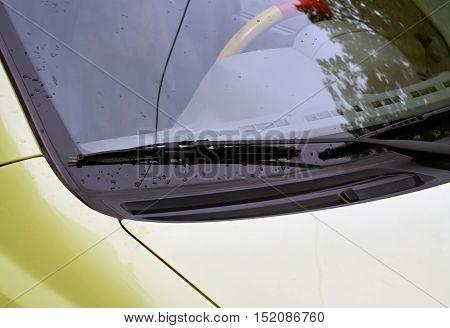 Closeup of car wiper in a rainy autumn day