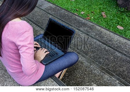 Asian freelance woman using laptop on steps outdoors
