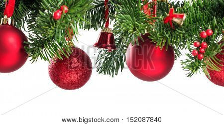 Close up of xmas red balls on fir branch with copy space. Christmas ornaments isolated on white background. Christmas tree pine branches with red balls and bells.