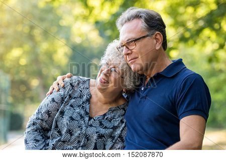 Portrait of a loving mature couple embracing at park. Senior couple sitting outdoor and thinking about retirement. Old man embracing elderly woman while she leans her head on his shoulder.