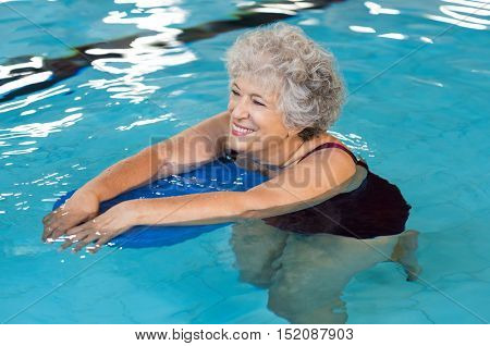 Happy senior woman with kickboard in a swimming pool. Old woman swimming in water with the help of a kickboard. Smiling old woman swimming with inflatable board in swimming pool.