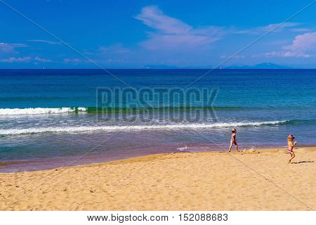 sea surf with a foamy wave and children go on the big sandy coast