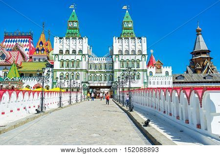 MOSCOW RUSSIA - MAY 10 2015: The white bridge leads to the splendid gate of Izmailovsky Kremlin decorated with fretwork details paintings and patterned towers on May 10 in Moscow.