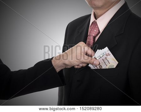 Businessman giving a bribe / money to the pocket for corruption something in dark tone with clipping path