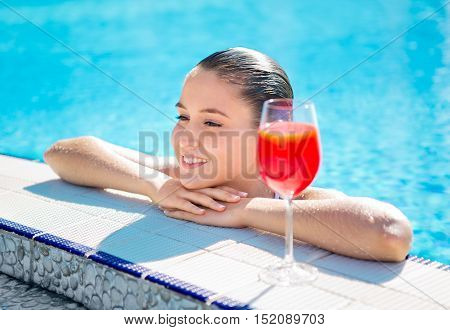 Young Woman Relaxing in the Swimming Pool with a Drink