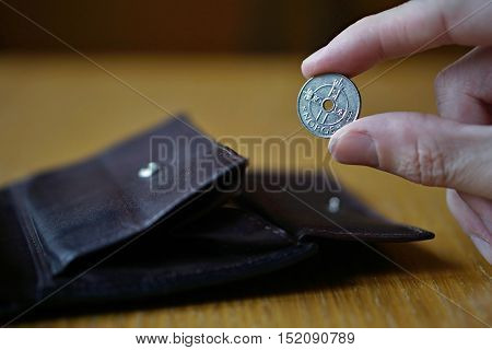 Male hand holding a silver Norwegian coin (currency in Norway, Norwegian krone, NOK) and withdrawing that from the brown leather wallet