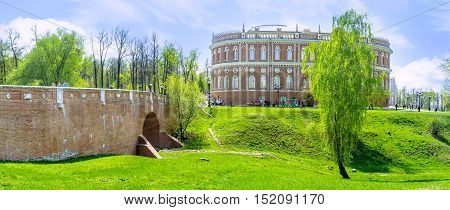 MOSCOW RUSSIA - MAY 10 2015: The Small (Greenhouse) Bridge over the ravine in Tsaritsyno Imperial Residence with the Bread House behind the birch tree on May 10 in Moscow.