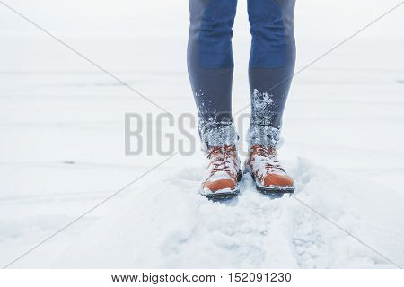 Legs Of Traveler Standing In Snow Outdoor. Travel And Discovery Concept