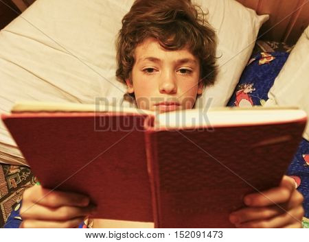 teenage handsome boy reeding book in bed close up photo