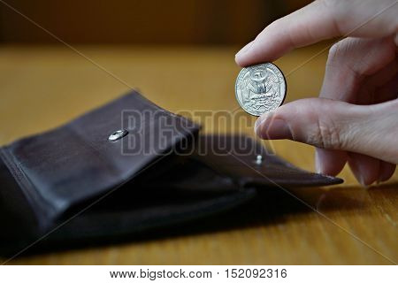 Male hand holding a silver Quarter Dollar coin (currency in the USA, American Dollar, USD) and withdrawing that from the brown leather wallet