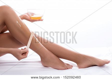 Preparation for beach season. Cropped photo of woman doing waxing depilation on her legs, isolated on white background