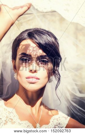 sexy bride woman with pretty face under wedding veil on sunny summer day outdoor closeup