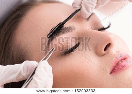 Plucking for perfection. Cropped shot of woman in white gloves using tweezers on patient eyebrow at health spa isolated on white background