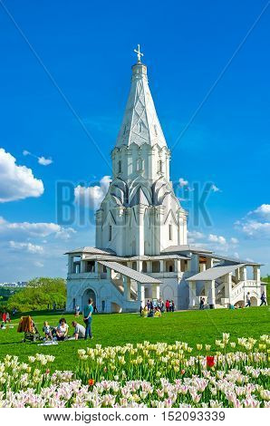 MOSCOW RUSSIA - MAY 10 2015: The meadow with white tulips in blossom in front of Ascension Church in Kolomenskoye is the best place to relax and enjoy the views on May 10 in Moscow.