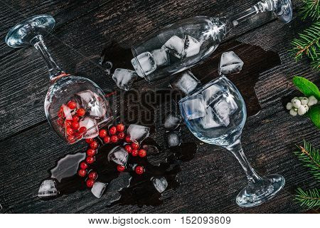 Wine glasses with ice cubes and red berries lying on the dark wood surface decorated with fur tree twigs. Flat lay