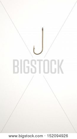 Fishing hook on a white paper background - closeup