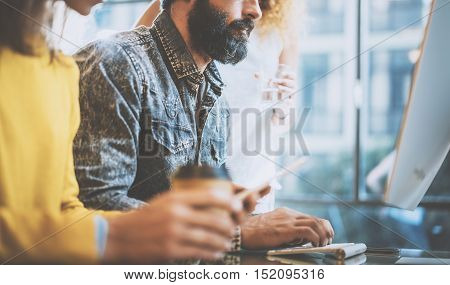 Bearded man typing on desktop keyboard in a sunny office near the windows. Young coworkers discussing business ideas at workplace.Horizontal, blurred background