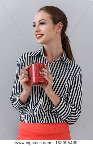 Time for coffee break. Portrait of young businesswoman drinking hot beverage and posing in studio, isolated on grey background