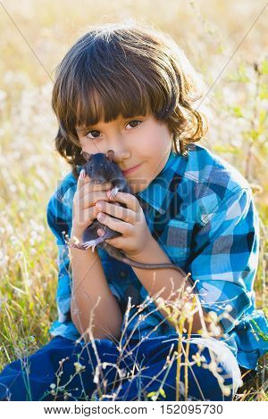 teenage happy boy playing with rat pet outdoor.