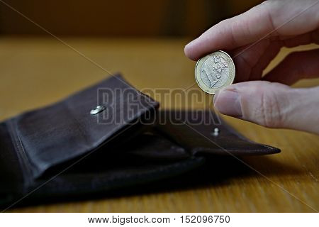 Male hand holding one Euro (European currency Euro, EUR) and withdrawing that from the brown leather wallet