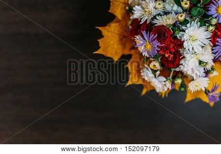 Bouquet of flowers and yellow autumn leaves on a dark wooden background blurred. patern. top view